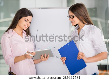 Two beautiful office workers drawing business strategy concept.