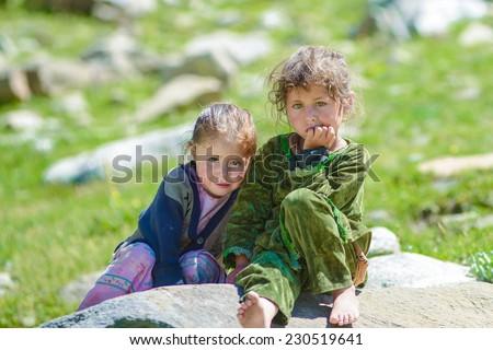 Two Beautiful Pakistani Girls Sitting on Stone - stock photo