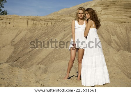 Two beautiful sensuality attractive and pretty girls friends - blond and brunette woman over sand background in white fashionable elegance dress - stock photo