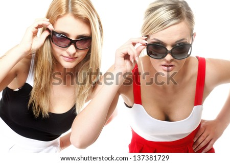 Two beautiful sexy crazy women in summer clothes and sunglasses. Studio shot isolated on white background