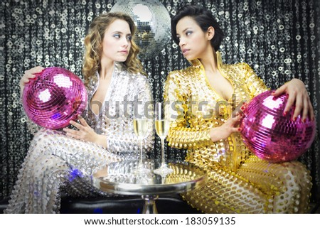 two beautiful sexy disco women in a bar lounge setting with champagne - stock photo