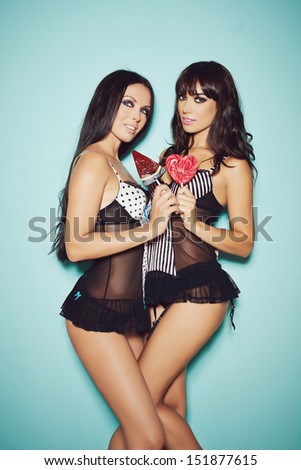 Two beautiful sexy girls in lingerie with candies on blue background - stock photo