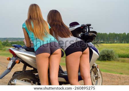 Two beautiful sexy girls seen from behind leaning on scooter on beautiful summer day. - stock photo