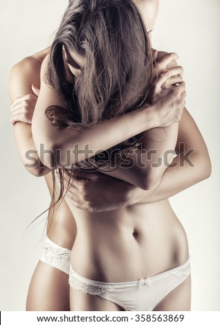 Two beautiful sexy lesbian women in erotic foreplay game on a white background - stock photo