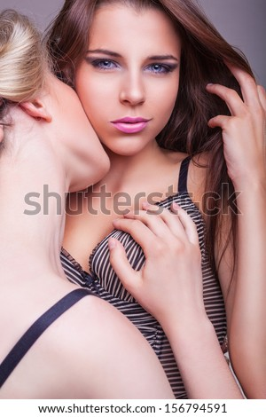 Two beautiful sexy lesbian women in erotic foreplay game on grey background - stock photo