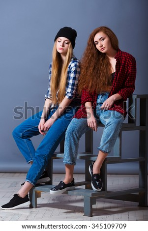 Two beautiful sexy young girls in jeans. Fashion portrait of girlfriends on grey background.