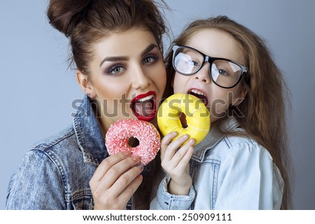 Two beautiful sisters (girls)  in hipster style clothes and in glasses eat cupcakes  at studio.  Perfect skin and make up.  Casual clothes.  - stock photo