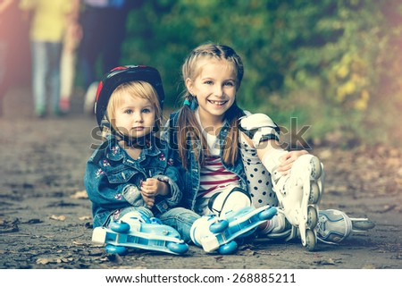 two beautiful sisters on roller skates in park - stock photo