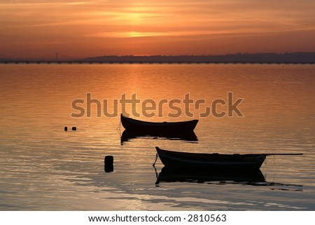 Two beautiful small boats at sunset in harbor - stock photo