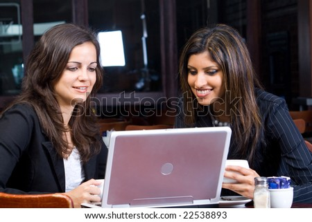 two beautiful smiling businesswomen in cafe with laptop and papers - stock photo