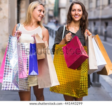 Two beautiful smiling girls holding shopping bags walking at street
