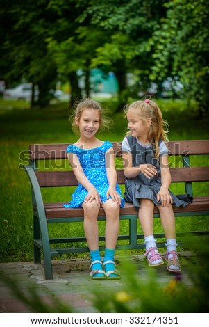 Two beautiful smiling little sisters sit on a bench in summer green city park. - stock photo