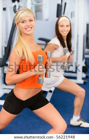 Two beautiful smiling sportswomen do exercises with dumbbells in big sports hall. - stock photo