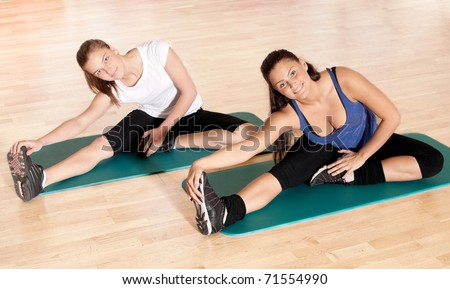 Two beautiful sport woman doing stretching fitness exercise at sport gym. Yoga - stock photo