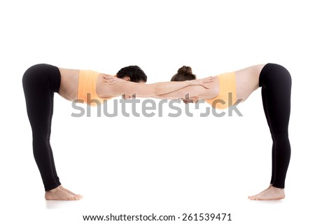 Two Beautiful Sporty Girls Practice Yoga Together In Orange Bright Sportswear Warming Up Standing