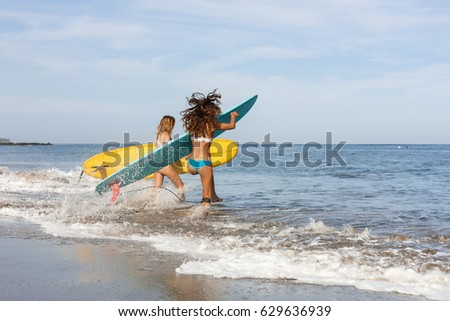 Two beautiful sporty surfing girl running into the sea waves with lot of sparks with big longboard surf surfboard board on sunrise or sunset. Modern active sport lifestyle and summer vacation.