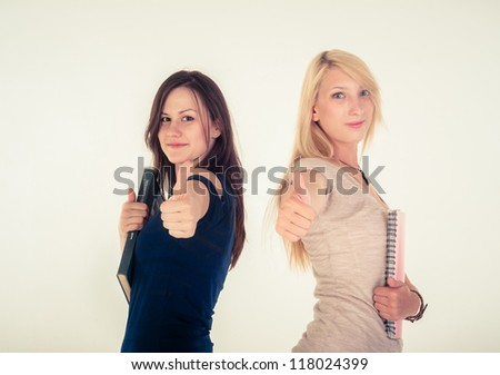 Two beautiful student girls showing thumbs up against white background