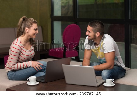 Two Beautiful Students Drinking And Having Fun With Laptop In Cafeteria - stock photo