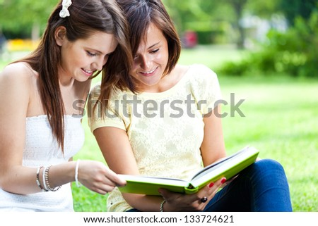 Two beautiful students reading a book on the grass - stock photo