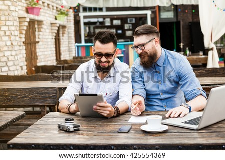 Two beautiful stylish bearded businessman with glasses in a vintage cafe negotiating, working on laptop computer, holding a tablet, documents, notebook, pens pencils, drink coffee mobile phone hipster - stock photo