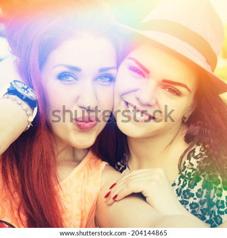 Two beautiful teenage female friends taking a selfie. Instagram filter. Square image. Closeup. Color light leak. Self portrait. - stock photo
