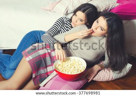 Two beautiful teenage girls eating popcorn and watching movies late at night. - stock photo