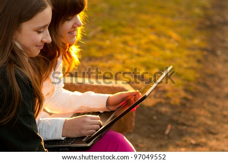 Two beautiful teenage girls having fun with notebook in the park on sunny spring day. - stock photo