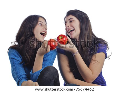 Two beautiful teenage girls hold red apples, face each other, and laugh. Horizontal layout with copy space and isolated on white background.