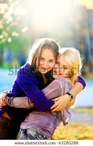 two beautiful teenage girls hugging in the autumn park - stock photo
