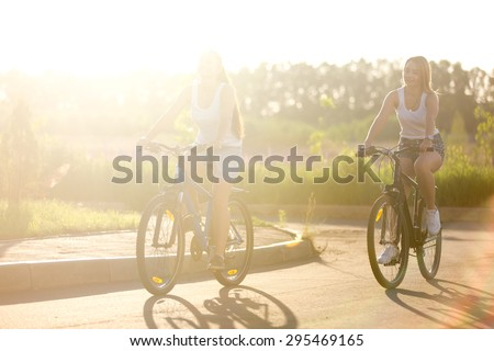 Two beautiful teenage girls riding bikes on park track wearing casual white tank tops and jeans shorts on bright sunny summer day, full length - stock photo