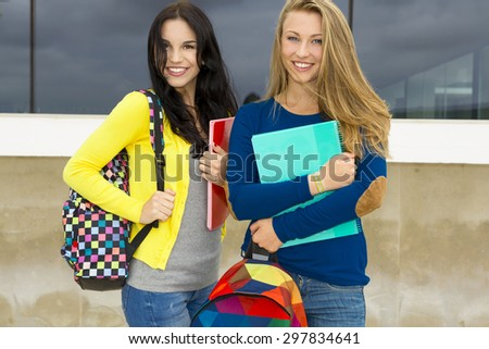 Two beautiful teenage students holding backpacks and smiling