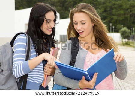 Two beautiful teenage students studying and showing something in the books - stock photo