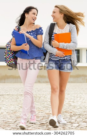 Two beautiful teenage students walking together in the school - stock photo
