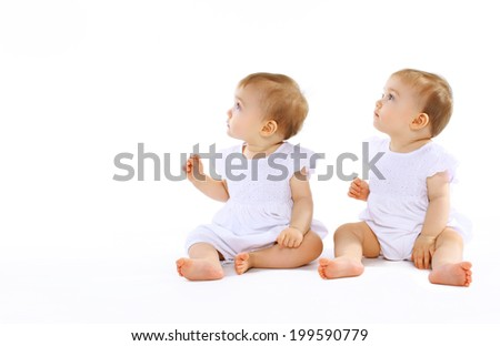 Two beautiful twins baby looking away - stock photo