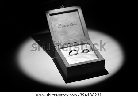 Two beautiful wedding lying in square wooden present box with text of love is as symbol of happy marriage in round light on black background with no people, horizontal picture - stock photo