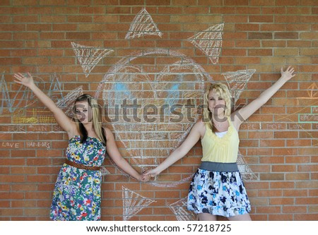 Two beautiful white Caucasian blond girls standing beside a heart design written with chalk on a brick wall.