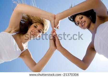 two beautiful woman best friends on beach having fun - stock photo