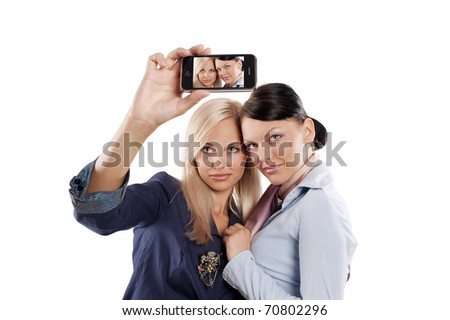 two beautiful woman in formal dress looking at a smart phone and taking photo - stock photo