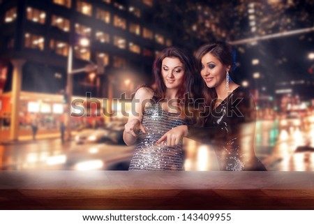 Two beautiful woman looking in the shopwindow on the night city street - stock photo