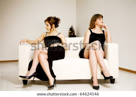 two beautiful woman sitting on the different sides on sofa