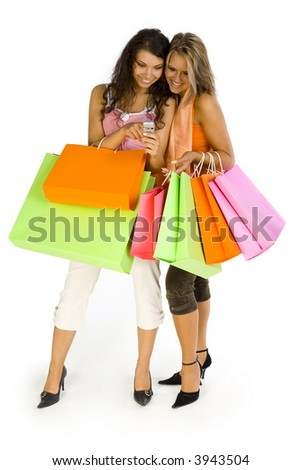 Two, beautiful woman standing and holding bags and mobile phone. Smiling and looking at phone. Isolated on white in studio, whole body. - stock photo
