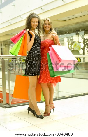 Two, beautiful woman standing in big shop, holding bags and smiling. Looking at camera, whole body