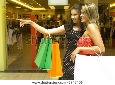 Two, beautiful woman standing in front of exhibition in big shop. One woman is showing something. Whole body - stock photo
