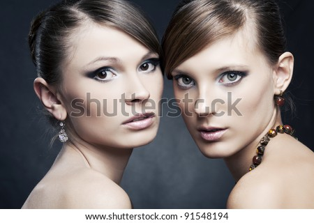 two beautiful woman with perfect skin,  bright trendy makeup in black dress with jewelry
