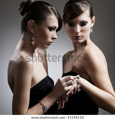 two beautiful woman with perfect skin in black dress with jewelry - stock photo
