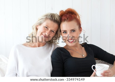 Two beautiful women-a mother and daughter sitting on the sofa at home, snuggled. They drink coffee, tea. Relationships and shared time. - stock photo