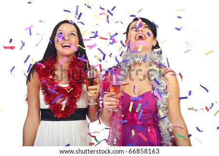 Two beautiful women celebrate new year party with champagne and confetti and laughing together - stock photo