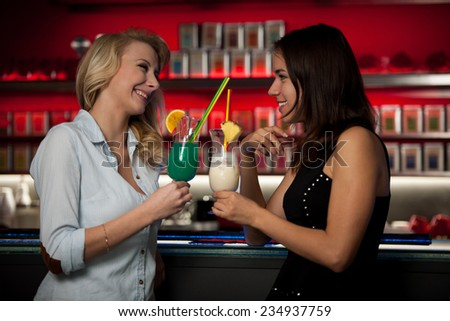 Two beautiful women drinking cocktail in a night club - stock photo