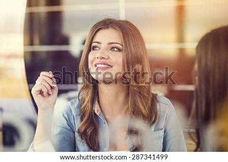 Two beautiful women drinking coffee and chatting in cafe - stock photo
