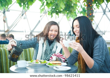 Two beautiful women drinking coffee, having lunch and chatting at cafe - stock photo
